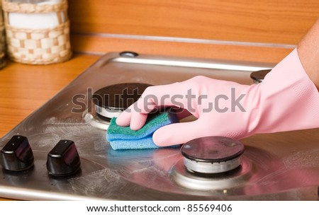 hand of the person in a rubber glove cleans a kitchen gas cooker