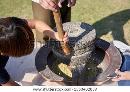 Hand of the person who is spinning a Korean millstone