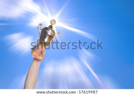 Hand of the person with a sports cup on a background of the bright sky.