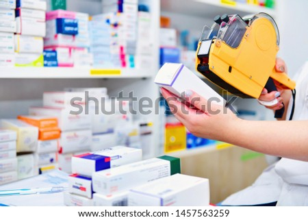 Hand of the pharmacist using yellow labeling gun for sticking price label of medicine in pharmacy drugstore.