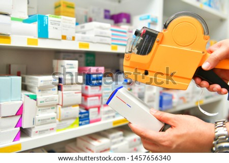 Hand of the pharmacist using yellow labeling gun for sticking price label of medicine in pharmacy drugstore
