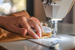 Hand of the seamstress is using a white industrial sewing machine to sew yellow cloth.