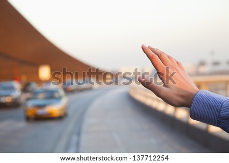 Hand of traveler hailing a taxi outside of the airport