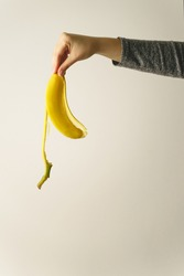 Hand of unknown caucasian woman holding banana peel in front of white wall - copy space concept of ending and finish trash ready to be thrown away old habit and new beginning