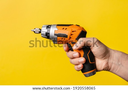 Hand of unknown man holding electric screwdriver - male hold work craft tool on bright yellow background - repair renovation electric equipment tools modern concept Foto stock ©
