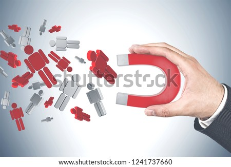 Hand of unrecognizable businessman wearing a suit using horseshoe magnet to attract red and white people figures over gray wall background. Hr concept