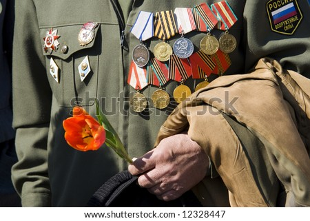 hand of war veteran with tulip on Victory Day in Russia (editorial photo, focus point on hand)