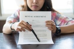 Hand of woman broker shown to client where to sign signature contract.