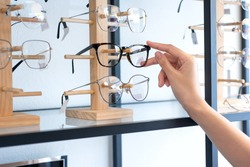 Hand of  woman choosing the glasses in optics store, eyesight and vision concept