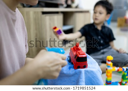 Hand of woman is spraying alcohol antiseptic,disinfecting toys,cleaning toys at home,disinfection,health care during a pandemic of Coronavirus,Covid-19,wipe dirt,clean to protection contagious disease