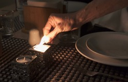 Hand of woman lighting candles for popular Shabbat meal on friday night dinner. Jewish day of rest tradition