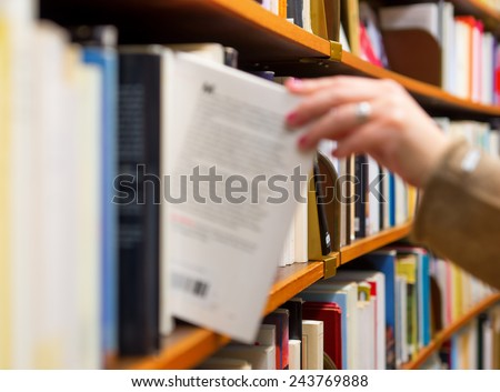 Hand of woman selecting a book from book shelf, blurred motion #243769888