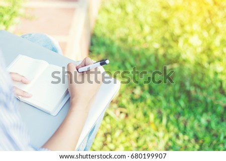 Hand of woman' using a pen for writing in her notebook for outdoor working her business in the park. #680199907