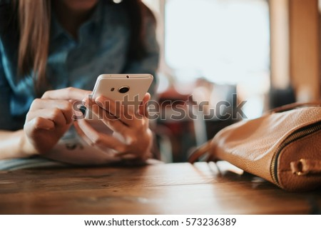Hand of woman using smartphone on wooden table,Space for text or design. #573236389