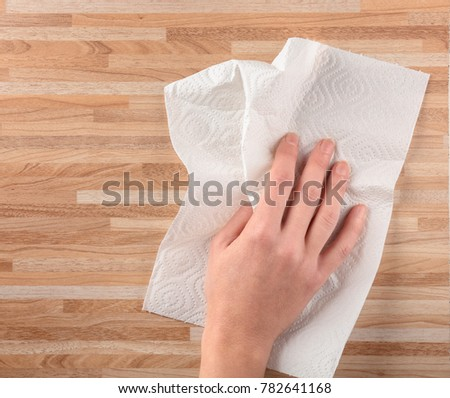 Hand of woman wiping wooden surface with paper towel