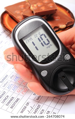 Hand of woman with glucose meter and portion of chocolate on medical form with results of measurement of sugar, concept of measuring sugar level