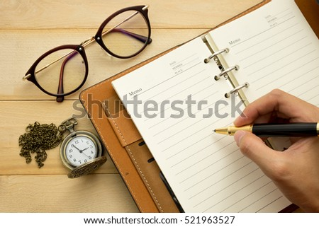 hand of women writting on diary book