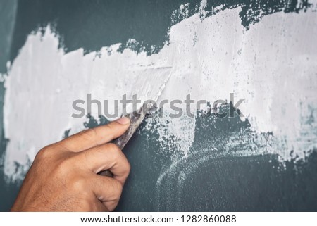 hand of worker holding trowel and applying skim coat plastering on a wall #1282860088