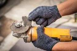 hand of worker man hold Grinder blades broken . Dangers of using power tools