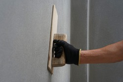 hand of worker plastering cement wall at construction site with copy space, selective focus