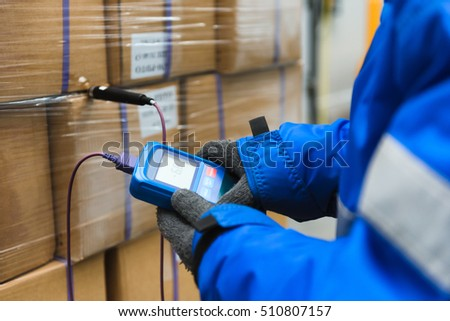 Hand of worker using thermometer to temperature measurement in the goods boxes with ready meals after import in the cold room or warehouse for keep temperature room.