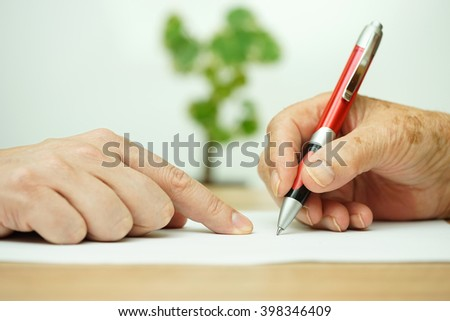 Hand of young adult pointing  elderly person where to sign