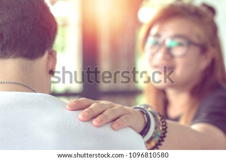 hand of young asian woman touching shoulder of young man to comforting her boyfriend.