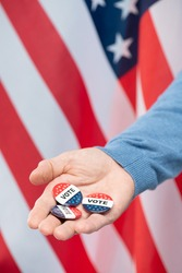Hand of young contemporary manager or businessman showing group of vote insignias against stars-and-stripes background in isolation
