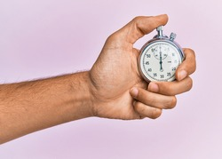 Hand of young hispanic man using stopwatch over isolated pink background.