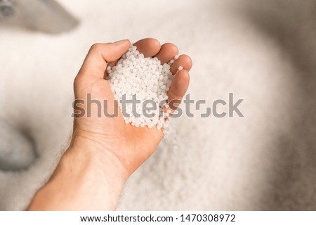 Hand of young male worker of large modern factory holding polymer granules