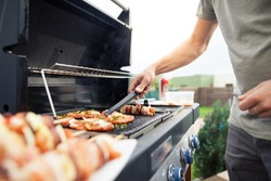Hand of young man grilling some meat and vegetable-meat skewers on huge gas grill (Shallow DOF)