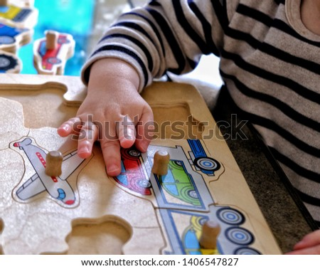 Hand of young toddler placing wooden puzzle piece in place. Educational child's toy #1406547827