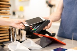 Hand of young woman holding smartphone close to electronic payment machine while paying for food in cafe