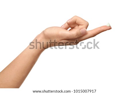 Hand of young woman with cream on finger, against white background