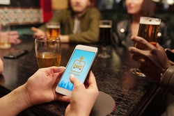 Hand of young woman with smartphone over table going to call for taxi against group of friends having drinks and discussing their plans