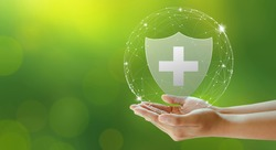 Hand offer medical shield on green background. Family life insurance, Medical care insurance, and Business healthy concepts. Copy space.