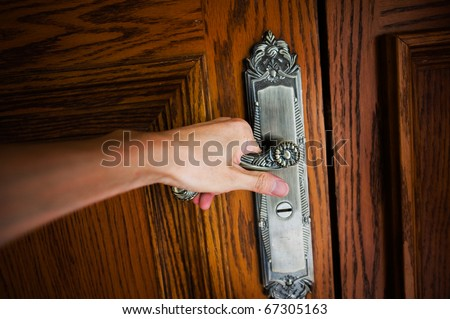Hand on a handle wooden door to open or close it.