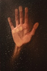 hand on a wet window with raindrops. loneliness