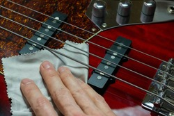 Hand on an electric bass guitar with a cleaning microfiber cloth