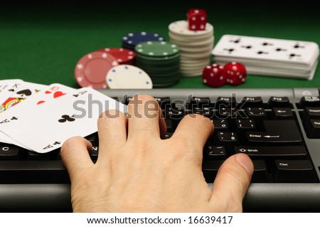 hand on computer keyboard with playing cards chips and dices in background