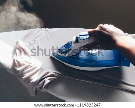 Hand on electric stream iron ironing the t-shirt. #1119823247
