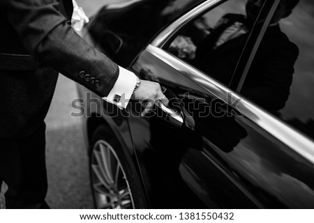 Hand on handle. Close-up of Asian man hand opening / close a car door, chauffeur car service background concept Photo stock ©
