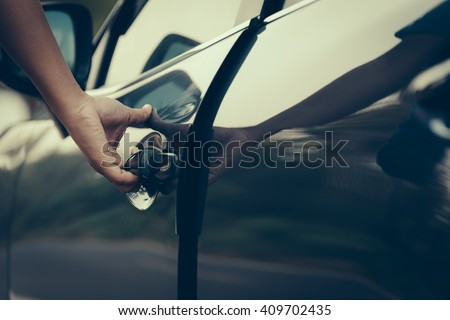 Hand on handle. Close-up of man hand opening a car door. vintage picture style process.