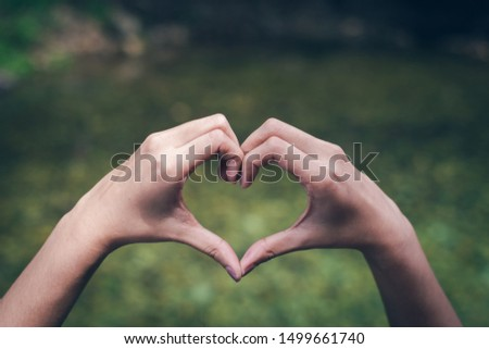 Hand on heart-shaped outdoor On a green natural background #1499661740