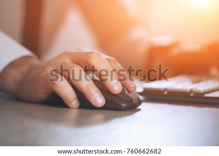 Photo of  Hand on mouse. Businessman computer. Business success, contract and important document, paperwork or lawyer concept. Man in office. Warm glare of sun light for text and design.