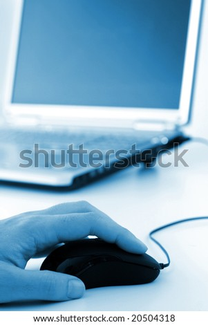 Hand on mouse with partial laptop in background in blue tint