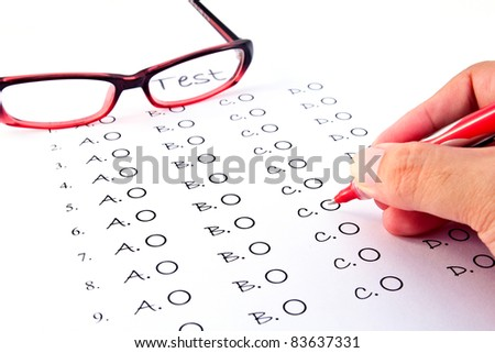Hand on pen choosing the test list and glasses on the examination