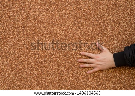 Hand on the wall. Abstract background texture - male hand is located in the lower right corner, on the wall surface covered with red-brown textured plaster. #1406104565