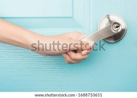 Hand open door knob blue background Foto stock ©