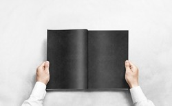 Hand opening black journal with blank pages mockup. Arm in shirt holding grey magazine template mock up. Man reading double-pages book first person view. Mag layout spread